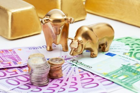 Golden bear, bull figurines with euro coins  gold bars on fanned