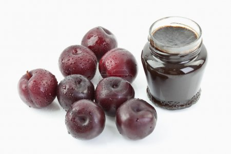 Plums beside open jar of plum jam on white background,close up