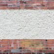 Outside wall with plastered area between red clink...
