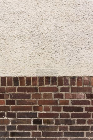 Outside wall with plastered top on red clinker bri...