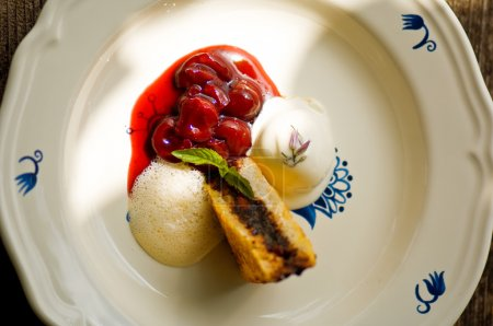 French toast cherries and ice cream on plate, elevated view