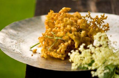 Baked elderflowers on plate, close-up