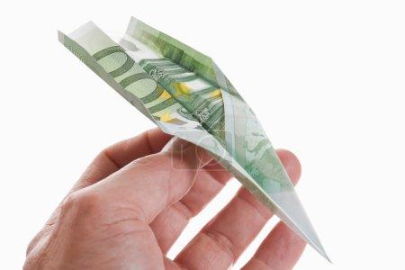 Personne qui détient l'avion de papier pliée de 100 Euro banknote, cl