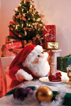Plush Santa Claus sitting at table, christmas tree and christmas