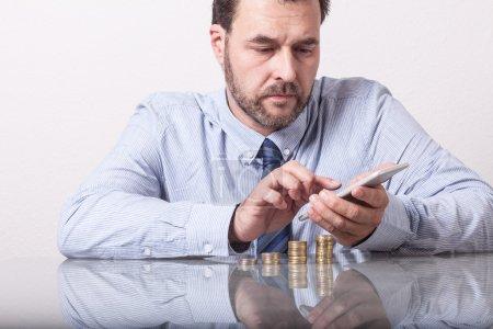 Photo pour Homme mûr au bureau avec des pièces en euros empilées en utilisant un téléphone intelligent - image libre de droit