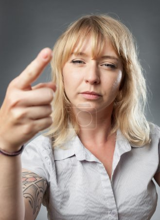Young woman portrait on grey background, threatening with finger