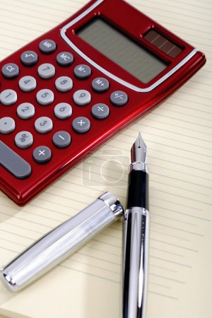 Pen and pocket calculator lying on a sheet