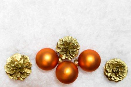 Orange baubles and golden fir cones in artificial snow, copy spa