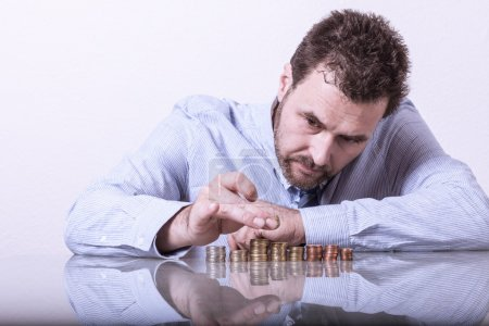 Business man counting money, stacks of coins on office desk