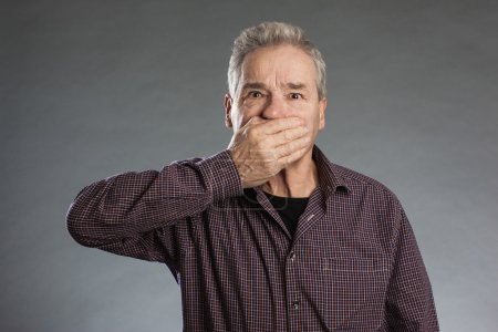 Male senior holding hands over mouth.