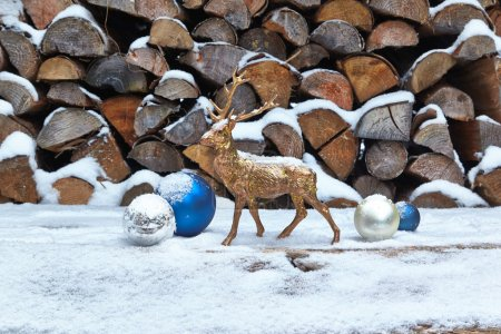 Deer figurine and baubles in snow, woodpile
