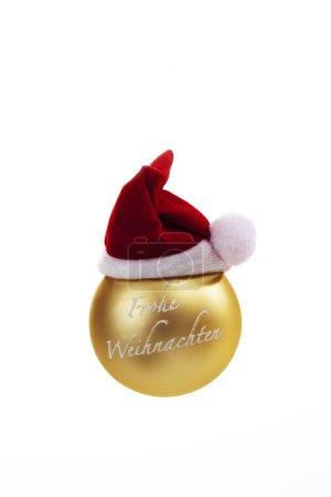 Photo pour Boule de Noël dorée avec chapeau de Père Noël sur le dessus sur fond blanc - image libre de droit