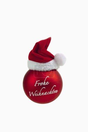 Photo pour Sphère de Noël rouge avec chapeau de Père Noël sur le dessus sur fond blanc - image libre de droit
