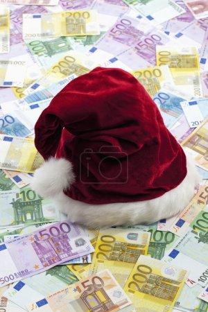 Photo pour Chapeau de Père Noël sur tas de billets en euros - image libre de droit