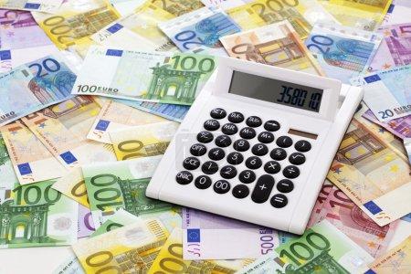 Photo pour Calculatrice sur tas de billets en euros - image libre de droit