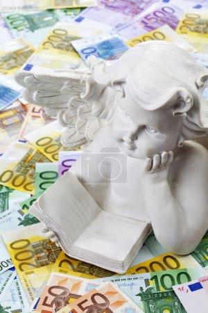 Photo pour Sculpture d'ange blanc sur tas de billets en euros - image libre de droit