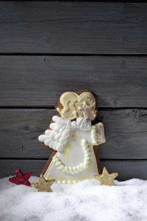 Photo for Gingerbread christmas angel star shaped decorations on heap of snow against wooden background - Royalty Free Image