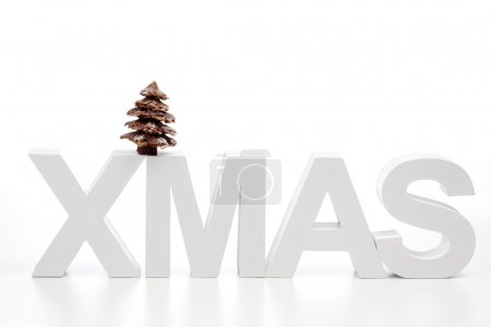 Photo for Capital letters forming the word xmas on top chocolate christmas tree against white background - Royalty Free Image