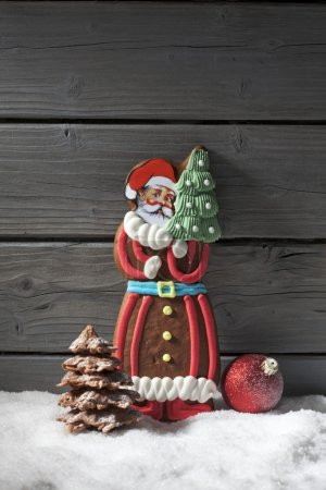Photo for Gingerbread santa claus christmas bulb chocolate christmas tree on heap of snow against wooden background - Royalty Free Image