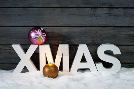 Photo for Capital letters forming the word xmas on top christmas bulb on pile of snow against wooden wall - Royalty Free Image