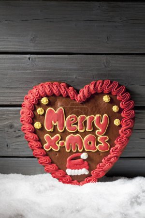 Photo for Gingerbread heart on heap of snow against wooden background - Royalty Free Image