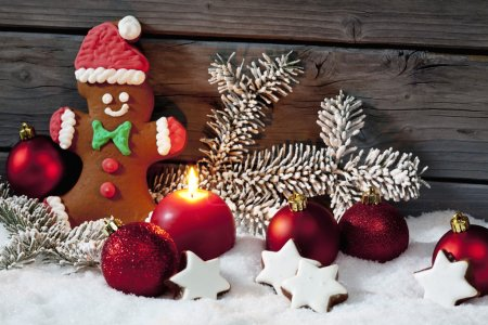 Photo for Christmas gingerbread bear, christmas bulbs, cinnnamon stars, pine twig and candle on pile of snow against wooden wall - Royalty Free Image
