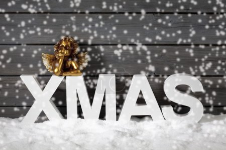 Photo for Capital letters forming the word xmas and golden putto figurine on pile of snow against wooden wall - Royalty Free Image