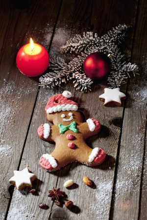 Photo for Christmas gingerbread man with candle cinnamon star nuts pine twig christmas bulb on wooden floor - Royalty Free Image