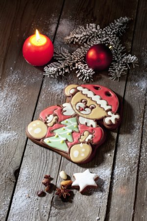 Photo for Christmas gingerbread bear with candle cinnamon star nuts pine twig christmas bulb on wooden floor - Royalty Free Image