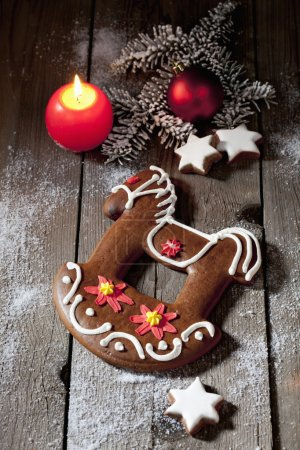 Photo for Gingerbread christmas horse with candle cinnamon stars pine twig christmas bulb on wooden floor - Royalty Free Image
