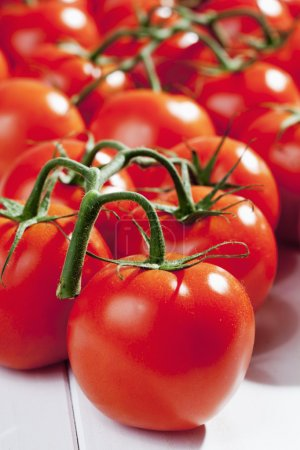 Photo for Bunch of vine tomatoes on white wooden floor - Royalty Free Image