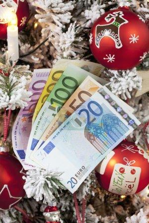 Photo pour Les billets en euros ventilés ferment l'arbre de Noël en arrière-plan - image libre de droit
