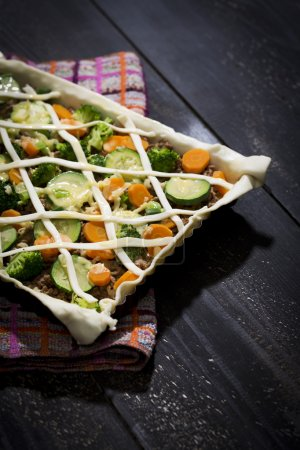 Puff pastry tart with mincemeat, broccoli, carrot and zucchini on baking tray