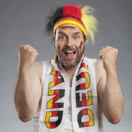 Ecstatic german soccer fan cheering clenching fists