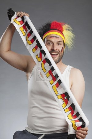 Ecstatic german soccer fan holding scarf Deutschland written on it