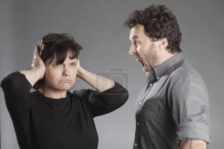 Mature couple quarreling man shouting woman covering ears