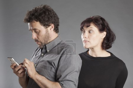 Mature couple man busy using smartphone woman looking curiously over man's shoulders