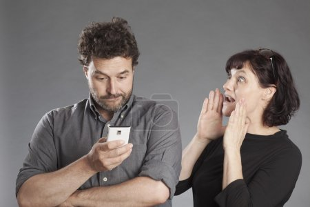 Mature couple man busy using smartphone woman shouting wanting attention