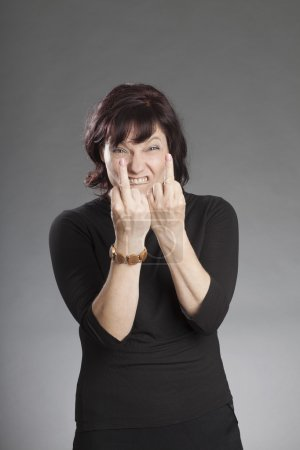 Mature brunette woman making faces against gray background