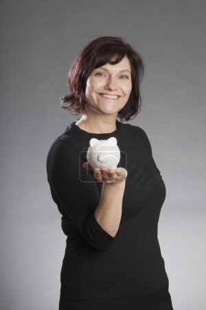 Mature brunette woman holding piggy bank against gray background