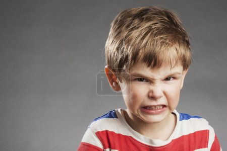 Young boy looking angry, clenching teeth against gray background