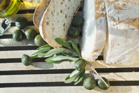Italy, Tuscany, Magliano, Close up of bread, olives and olive oil on chopping board, elevated view