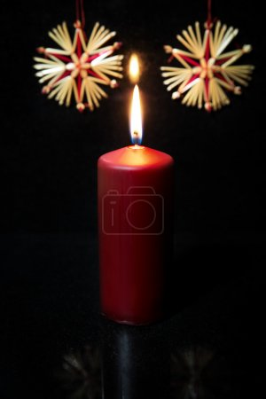 Red candle, straw stars, black background