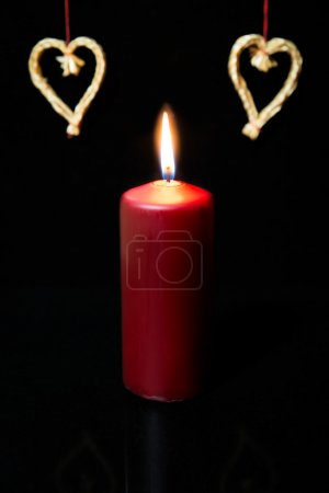 Red candle and straw hearts,