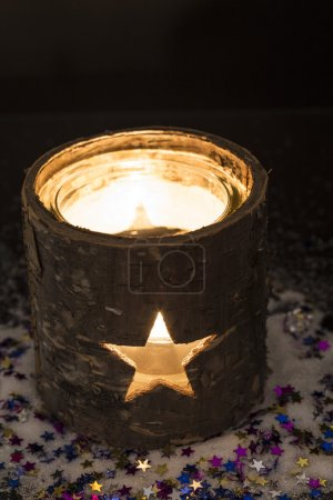 Photo for Burning candle in tea light holder with stars - Royalty Free Image