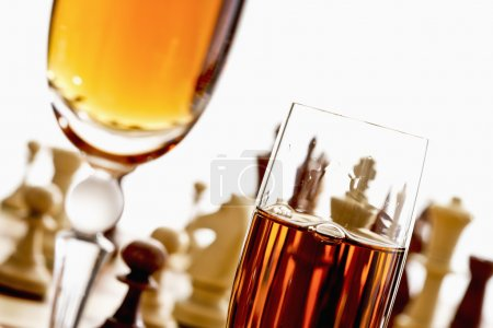 Sherry glasses in front of chess board