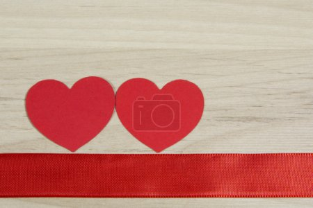 Photo for Red hearts with ribbon on wooden background - Royalty Free Image