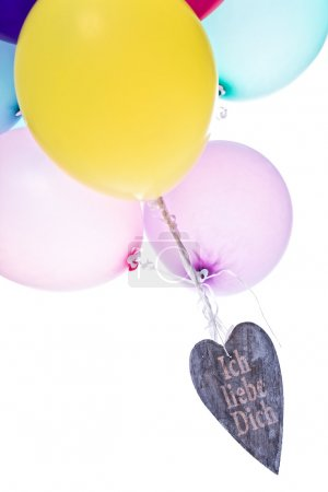 Colorful balloons with wooden heart