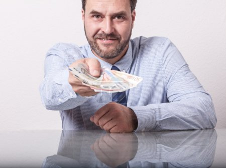 Mature man offering fanned euro notes