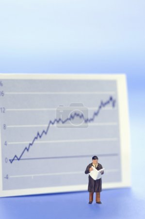 Figurine of businessman in front of graph